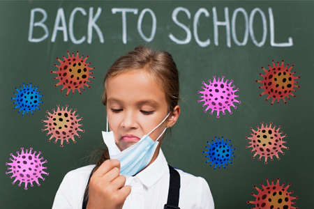 selective focus of displeased schoolgirl touching protective mask near chalkboard with back to school lettering and virus illustration