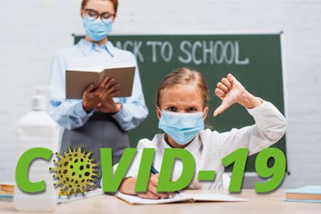 selective focus of displeased schoolgirl in medical mask showing thumb down, teacher standing near chalkboard with book near covid-19 lettering 免版税图像