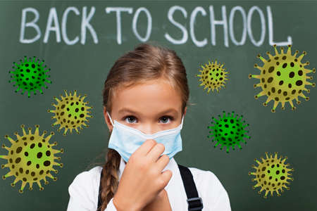 selective focus of schoolgirl touching medical mask near back to school lettering on chalkboard and virus illustration
