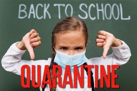 selective focus of displeased schoolgirl in medical mask showing thumbs down near chalkboard with inscription and quarantine lettering in classroom