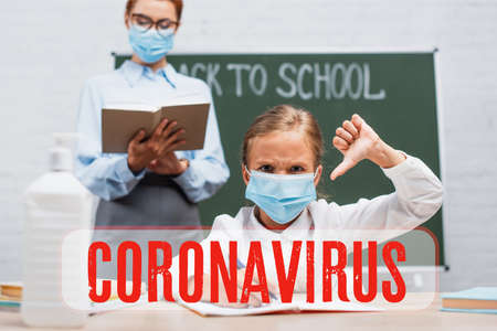 selective focus of schoolgirl in medical mask showing thumb down, teacher standing near chalkboard with book near coronavirus lettering 免版税图像