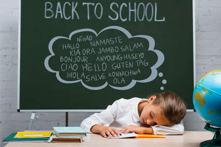 exhausted schoolgirl sleeping at desk near globe and chalkboard with back to school and greeting lettering 免版税图像