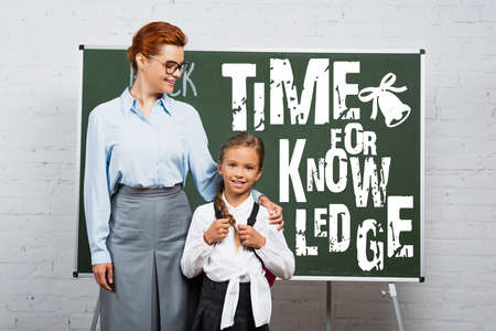 teacher and schoolgirl standing near chalkboard with time for knowledge lettering 免版税图像