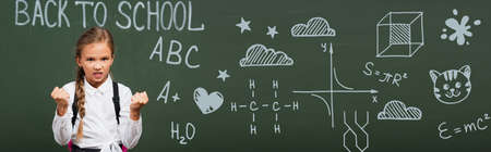 horizontal image of angry schoolgirl showing clenched fists near chalkboard with back to school lettering and geometry formulas in classroom