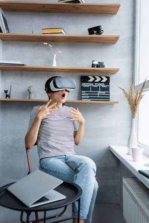 Selective focus of shocked woman in vr headset sitting near laptop on coffee table in living room