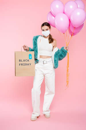 young woman in medical mask holding shopping bag with black friday lettering and balloons on pink