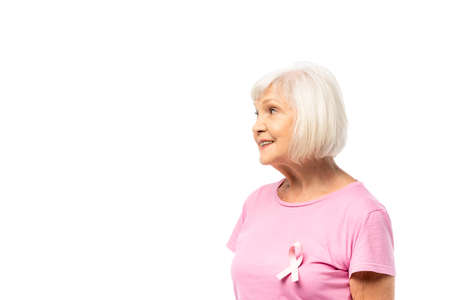 Gray haired woman with ribbon of breast cancer awareness on t-shirt looking away isolated on white
