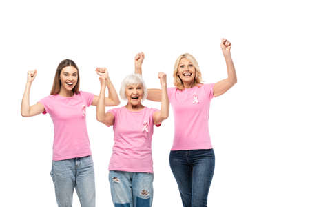Excited women showing yeah gesture at camera while wearing ribbons of breast cancer awareness isolated on white