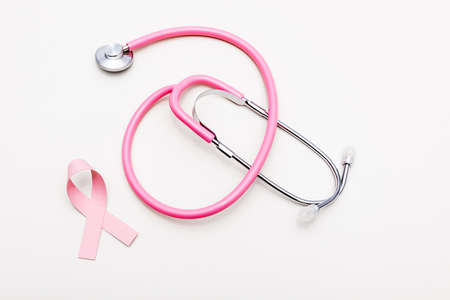 Top view of stethoscope and ribbon of breast cancer awareness isolated on white Archivio Fotografico