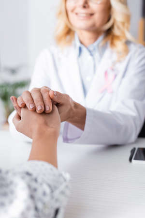 Selective focus of patient holding hand with doctor in white coat Imagens
