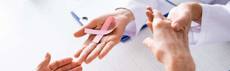 Panoramic shot of doctor holding patient hands and showing pink ribbon Archivio Fotografico