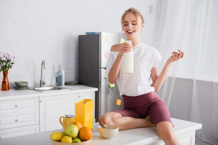 cheerful blonde woman holding bottle of milk while sitting on kitchen table near fruits 版權商用圖片