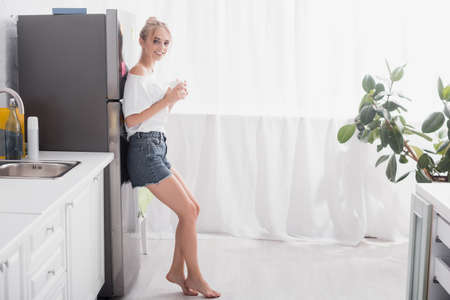 barefoot blonde woman standing near refrigerator with cup of tea 版權商用圖片
