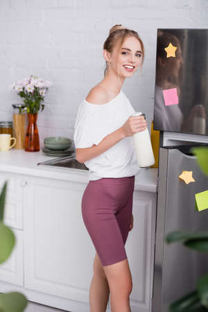 happy young woman in white t-shirt and shorts holding bottle of milk near opened fridge 版權商用圖片