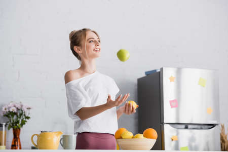 young woman in white t-shirt juggling with fresh fruits near teapot and cup in kitchen