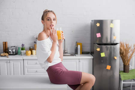 young blonde woman holding glass of orange juice and touching lips while sitting on table in kitchen