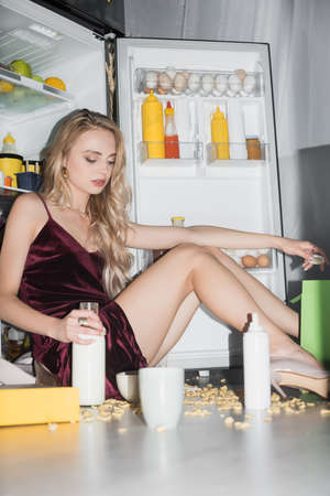 seductive woman in velor dress sitting on floor with bottle of milk near cornflakes scattered around