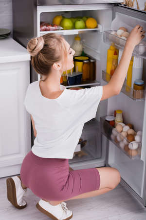 young woman in white t-shirt and shorts taking chicken eggs from refrigerator