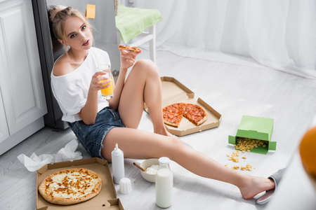 sensual young woman holding pizza and orange juice while sitting on floor in kitchen 版權商用圖片 - 157597506