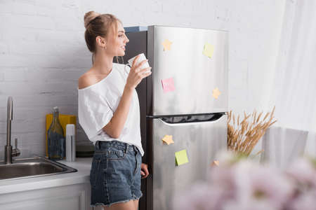 selective focus of blonde woman in white t-shirt and denim shorts standing in kitchen with cup of tea