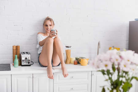 young barefoot woman in shorts sitting on kitchen table and looking at camera