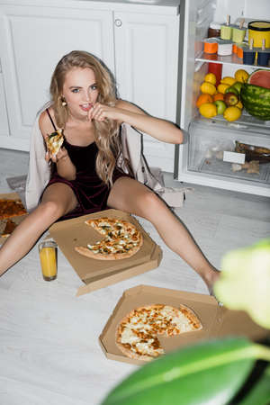 sensual woman in velor dress eating pizza while sitting on floor in kitchen near opened fridge 版權商用圖片