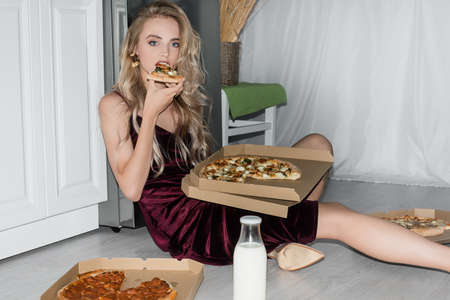 seductive blonde woman in velor dress looking at camera while sitting on floor in kitchen and eating pizza