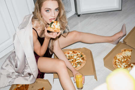 high angle view of blonde woman eating pizza and holding orange juice while sitting on floor and looking at camera 版權商用圖片