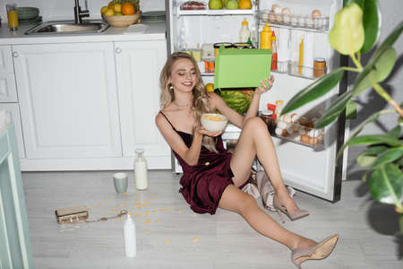 smiling woman in velor dress pouring cornflakes into bowl while sitting on floor near fridge