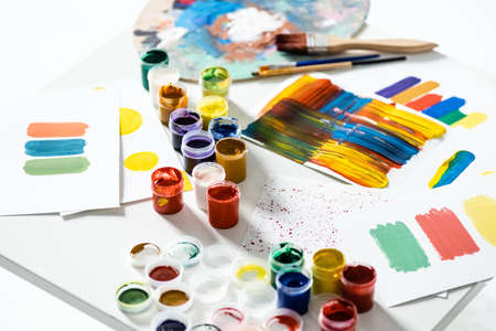 gouache paints, paintbrushes and abstract colorful brushstrokes on paper on white background 版權商用圖片
