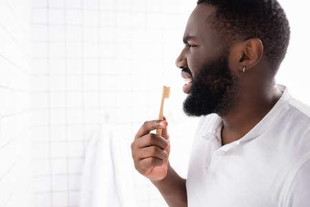 side view of unpleasant afro-american man brushing teeth