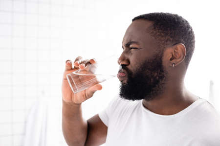 afro-american man grimacing and drinking water