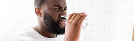 panoramic shot of afro-american man grimacing and drinking water
