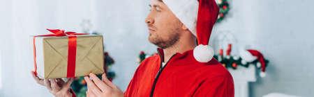 panoramic shot of man in santa hat holding chrismas gift box