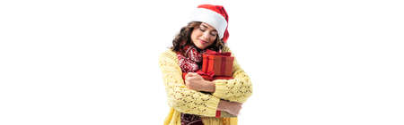 panoramic shot of joyful young woman in santa hat and scarf holding gifts isolated on white