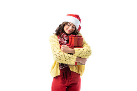 joyful young woman in santa hat and scarf embracing gifts isolated on white 写真素材