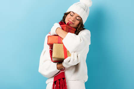 young brunette woman in winter outfit embracing presents on blue 写真素材