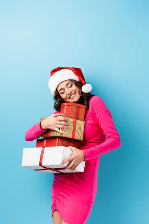 young joyful woman in santa hat and dress embracing wrapped presents on blue