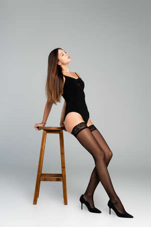 Sexy young adult woman in bodysuit and black stockings, looking away, while leaning on stool on gray