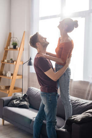 side view of young man hugging girlfriend standing on sofa at home 版權商用圖片