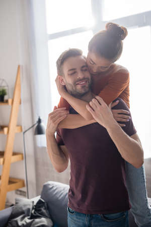 young woman hugging boyfriend from back while standing on sofa at home