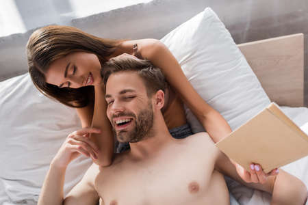 laughing shirtless man lying on smiling girlfriend holding book in bedroom