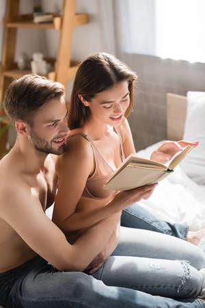 shirtless man hugging sexy girlfriend reading book in bedroom