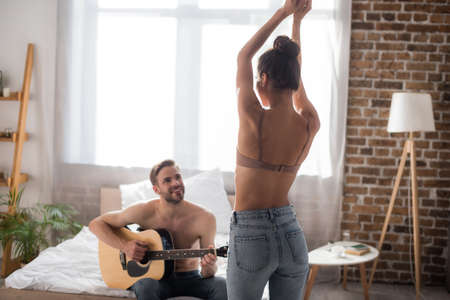 back view of sexy woman in bra and jeans dancing with raised hands in front of boyfriend playing guitar on bed