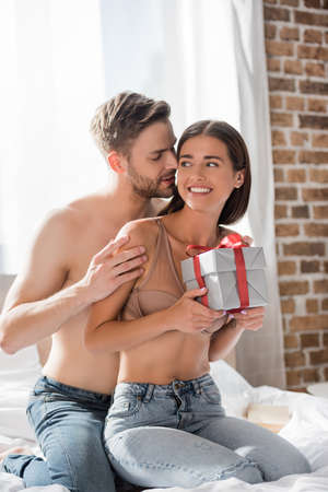 shirtless man hugging happy girlfriend holding gift box in bedroom