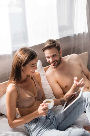 shirtless man pointing with finger near girlfriend holding digital tablet and cup of coffee