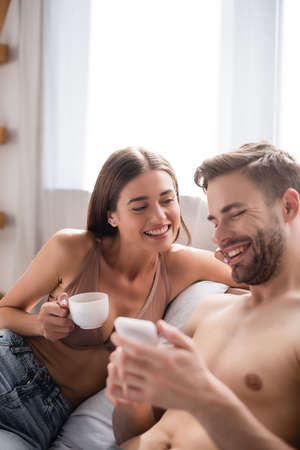 selective focus of woman holding cup of coffee while looking at cheerful boyfriend messaging on mobile phone on blurred foreground