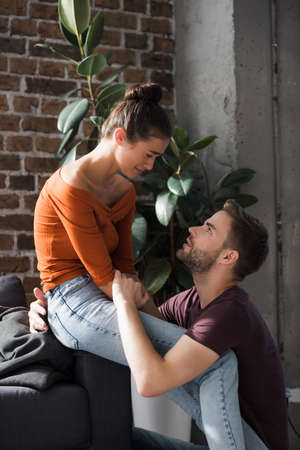 responsive man talking to upset girlfriend crying while sitting on sofa