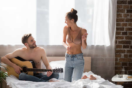 cheerful shirtless man playing guitar near girlfriend in jeans and bra dancing on bed
