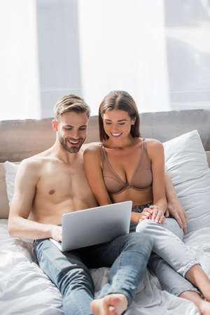 sexy smiling couple using laptop in bed together Zdjęcie Seryjne